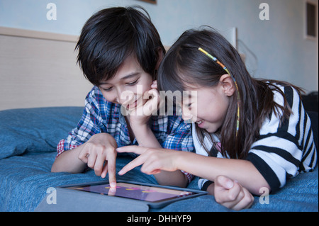 Brother and sister using digital tablet - Stock Photo