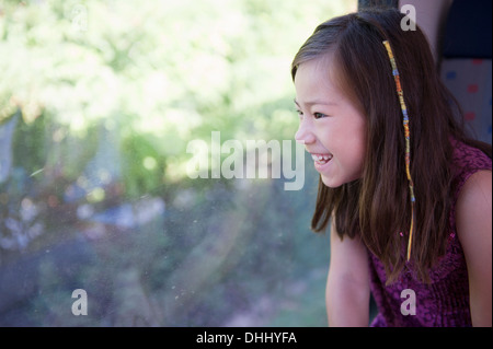 Girl looking out of train window - Stock Photo