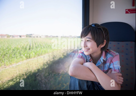 Boy looking out of train window - Stock Photo