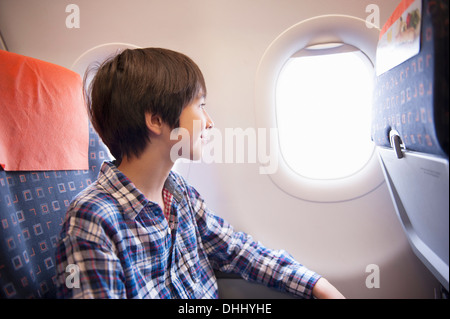 Boy looking out of window on aeroplane - Stock Photo