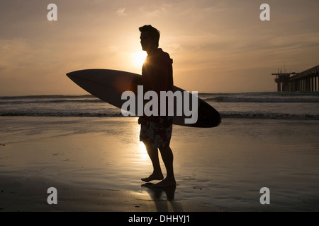 Surfer silhouetted on beach