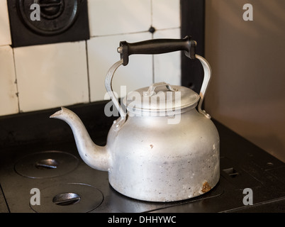 Old-fashioned metal kettle sitting on cast iron cooker hob - Stock Photo