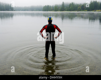 Young man in wet suit preparing to swim lake - Stock Photo