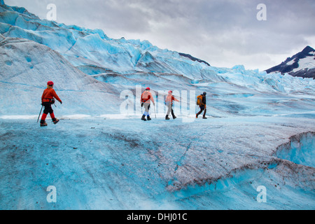 Four people walking on Mendenhall Glacier, Alaska, USA - Stock Photo