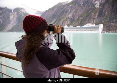 Woman using binoculars on cruise ship, Ketchikan, Alaska, USA