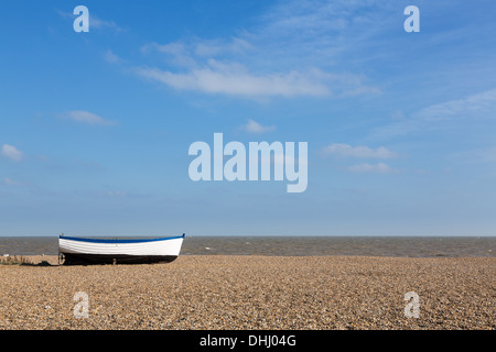 Aldeburgh beach in Suffolk, East coast of England, Uk with old wooden boat on the shingle - Stock Photo