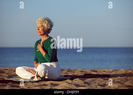 Senior woman in meditation by beautiful ocean. Eldery woman doing yoga on beach. - Stock Photo
