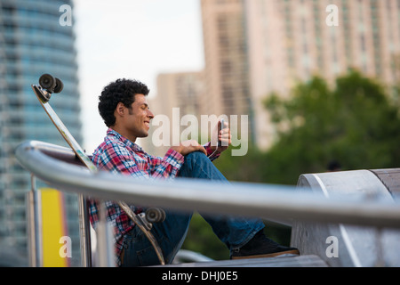 Man smiling at text message on mobile phone - Stock Photo