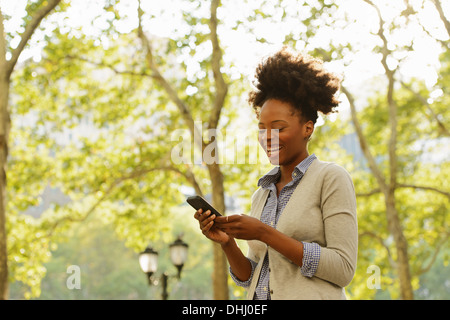 Woman smiling at text message on mobile phone - Stock Photo