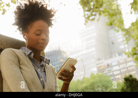 Woman listening to music on mobile phone - Stock Photo