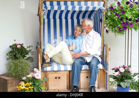 Retired couple relaxing on garden seat - Stock Photo