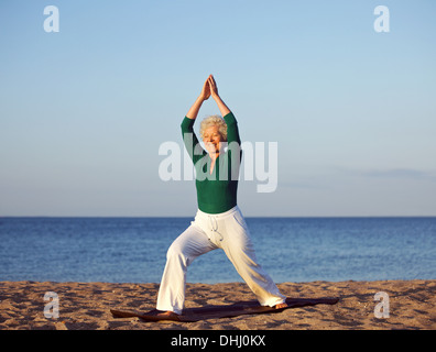 Senior woman stretching against beach background. Mature caucasian woman exercising on sandy beach in morning - Stock Photo
