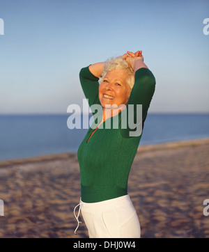 Happy elder woman looking relaxed on the beach with her hands on her head. Active senior female on the beach relaxing - Stock Photo