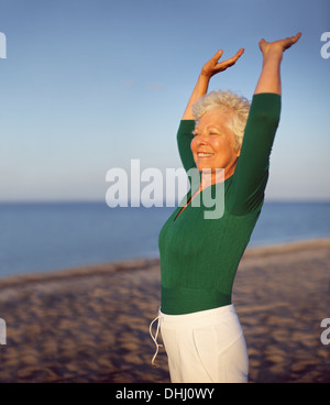 Portrait of beautiful mature woman practicing yoga on beach with copyspace. Old caucasian woman exercising outdoors - Stock Photo