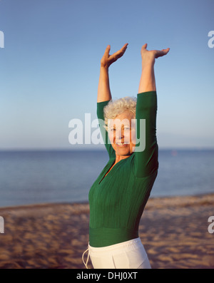 Portrait of healthy senior woman practicing yoga on beach with copyspace. Old caucasian woman exercising outdoors - Stock Photo