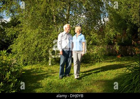 Portrait of senior couple in garden - Stock Photo
