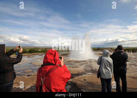 Tourists taking photos of the Strokkur geyser in the valley of Haukadalur at the golden circle, Iceland, Europe - Stock Photo