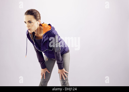 Young female runner with hands on knees. Tired young woman resting after jogging on grey background with lots of - Stock Photo