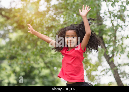 Young girl jumping and having fun in park - Stock Photo