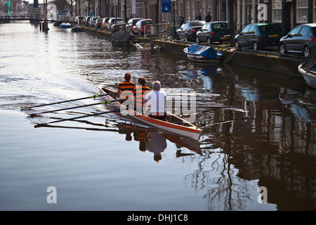 Three man scull on the Oude Vest canal in Leiden - Stock Photo