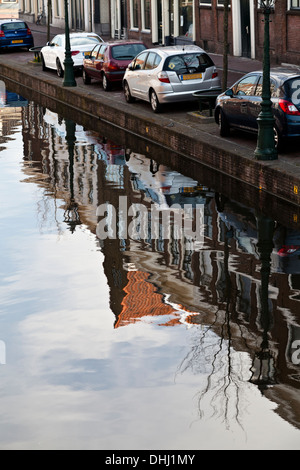 Beautiful reflections of buildings contrast with parked cars along the edge of the Oude Vest canal in Leiden - Stock Photo