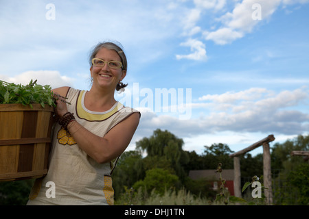 Portrait of woman working on herb farm - Stock Photo