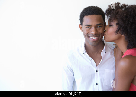 Portrait of young woman kissing man on cheek - Stock Photo