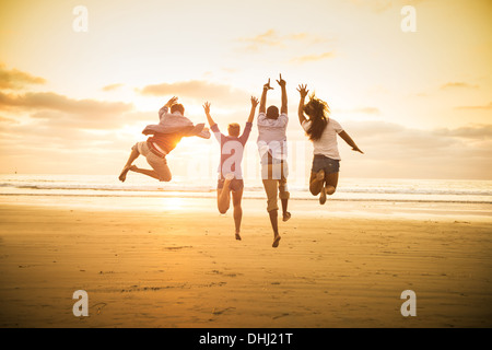 Young people jumping on Mission Beach, San Diego, California, USA - Stock Photo