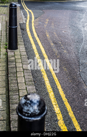 Street bollards and wobbly double yellow line, with patchy tarmac and fainted old lines - Stock Photo