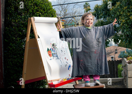 Girl outdoors painting on easel - Stock Photo