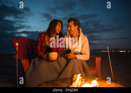 Young couple by campfire, San Diego, California, USA - Stock Photo
