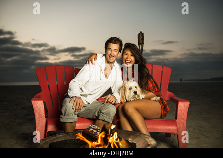 Young couple sitting by campfire on Mission Beach, San Diego, California, USA - Stock Photo