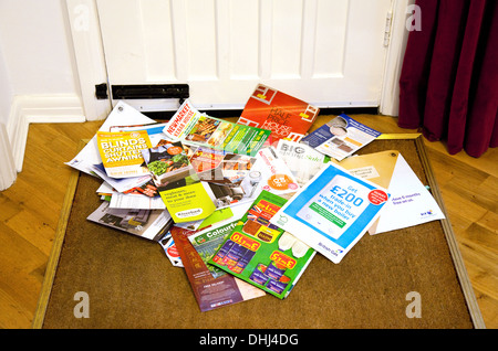 Junk mail on the doormat in a home, England UK - Stock Photo