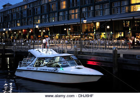 White boat, water taxi in front of the restaurants at the Finger Wharf, Woolloomooloo Bay, Sydney, New South Wales, - Stock Photo