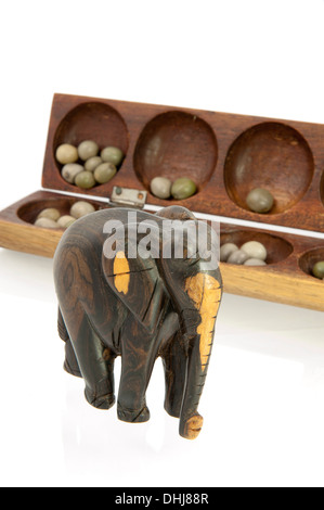 African elephant carved from tree with a wooden awale game - Stock Photo