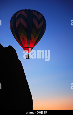 Hot air balloon near bluff, 'Dawn Patrol' event, Red Rock Balloon Rally, Gallup, New Mexico USA - Stock Photo