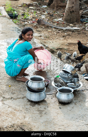 Young Indian woman washing dishes outside their rural indian village home. Andhra Pradesh, India - Stock Photo
