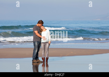 A pregnant woman and her partner standing on the beach - Stock Photo