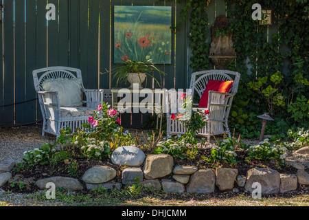 Two white garden chairs are placed next to a table and a painting ...