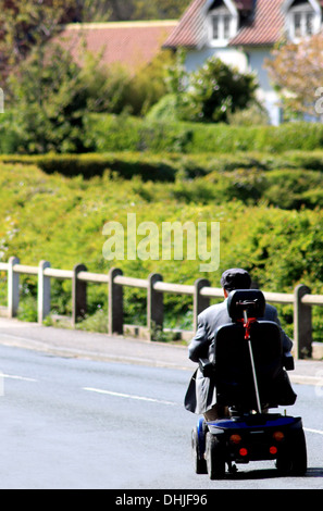 Rear view or senior man riding mobility scooter on countryside road. - Stock Photo