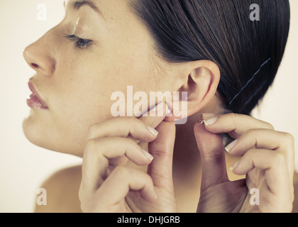 A young woman putting on an earring - Stock Photo