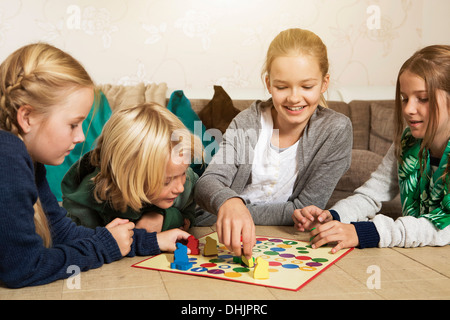 Four children playing ludo in living room - Stock Photo