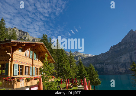 Chalet at lake Oeschinensee in the sunlight, Kandersteg, Bernese Oberland, Canton of Bern, Switzerland, Europe - Stock Photo