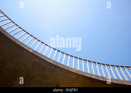 isolated abstract closeup view of curved pedestrian footbridge and railing against blue sky background - Stock Photo