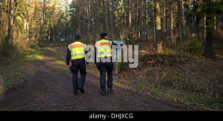 Karsdorf, Germany. 12th Nov, 2013. Policemen search a forest the defusing of several aerial bombs from WWII in the - Stock Photo
