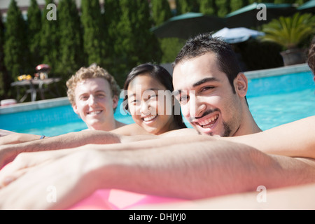 Portrait of four friends in the pool with an inflatable raft - Stock Photo