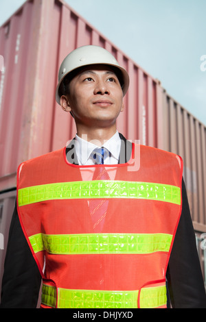 Proud engineer in protective workwear standing in a shipping yard - Stock Photo