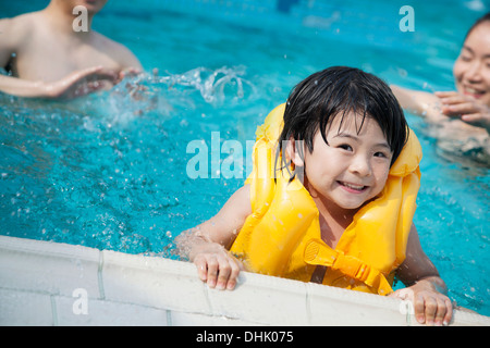 Portrait of smiling son in the water and holding onto the pools edge with family in the background - Stock Photo