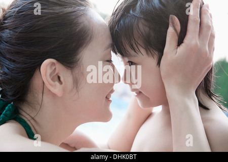 Smiling mother and son embracing and holding head by the pool - Stock Photo