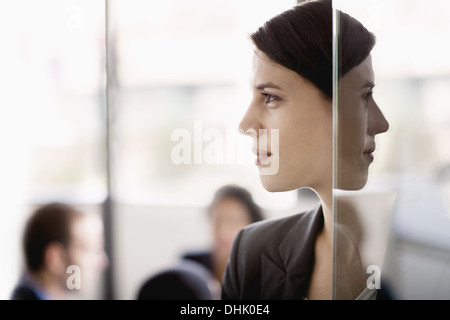 Side profile on a businesswoman with coworkers in the background - Stock Photo